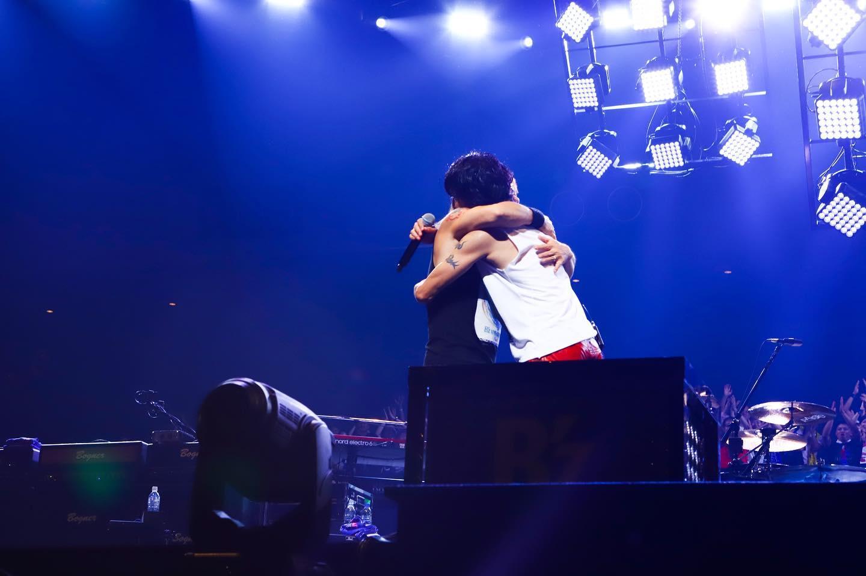 ステージ上で抱き合うB'z松本孝弘と稲葉浩志の写真