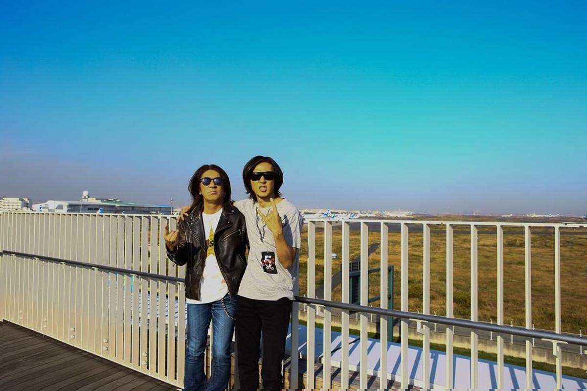 B'z公式SNSで公開された「足湯スカイデッキ」で肩を組む松本孝弘と稲葉浩志の写真